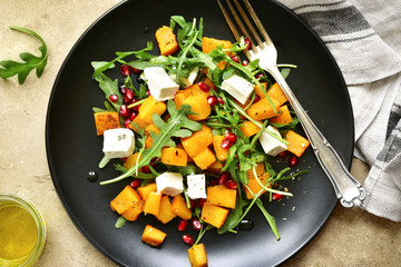 Delicious autumn pumpkin salad with arugula, feta cheese and pomegranate seeds.Top view.