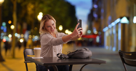 Peppy female taking selfie on phone while sitting at table on Champs-Elysees