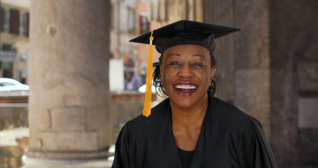 Portrait of senior black woman in graduation gown smiling and cheering