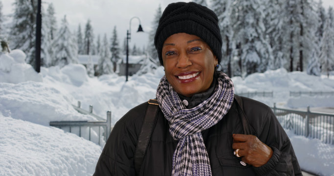 Portrait of cute senior black woman standing outdoors in the snow