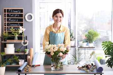 Female florist with roses at workplace