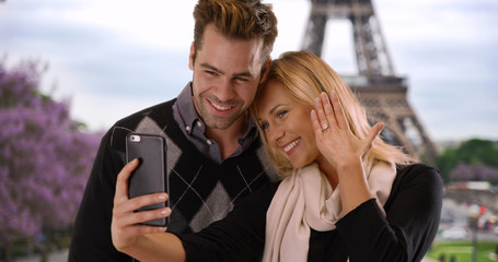 Joyful newly engaged couple take a selfie in Paris
