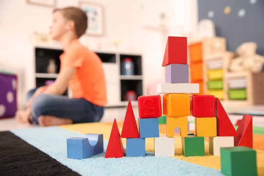 Castle made from cubes and little boy with autistic disorder on background