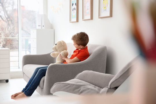 Little autistic boy sitting on sofa with toy at home