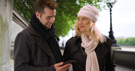 Couple using smartphone in London smiling