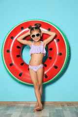 Cute little girl with inflatable ring near color wall