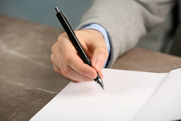 Writer signing autograph in book at table, closeup