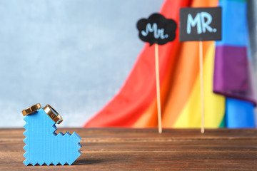 Heart figure with wedding rings and rainbow flag with photo booth props on background. Gay marriage