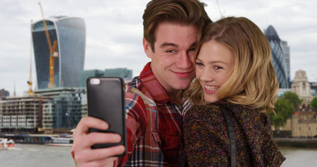 Cheerful young couple in urban setting taking a selfie with smartphone