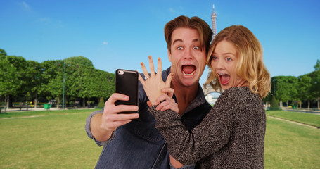Newly engaged couple taking a selfie in front of the Eiffel Tower smiling