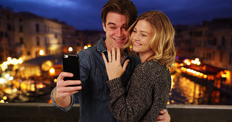 Newly engaged couple taking a selfie by the Grand Canal at night