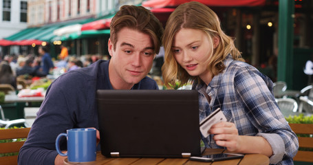 Happy Caucasian man and woman shopping online with computer