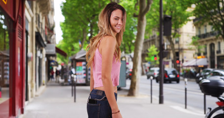 Carefree woman listening to music and dancing on Paris street