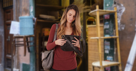 Happy and attractive female shopper looking at vintage purse