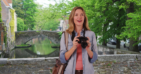 Travel photographer in Bruges taking picture outside smiling