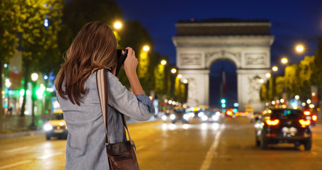 Rear view of travel photographer taking picture of Arc de Triomphe