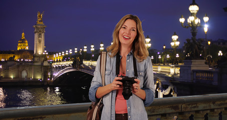 Travel photographer with her camera on gorgeous night in Paris