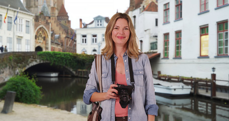 Portrait of woman tourist with her camera in Bruges