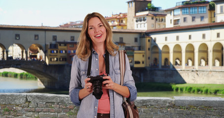 Portrait of woman tourist in Florence using camera on the Arno River in Florence