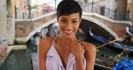 Beautiful smiling young black woman in Venice Italy posing in summer dress