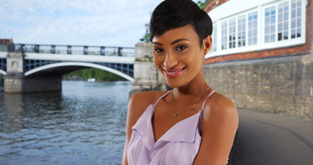 Beautiful smiling young black woman in Windsor England posing in summer dress