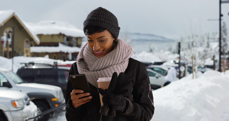 Beautiful young woman in the snow with coffee using smartphone