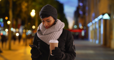 Pretty black woman with warm cup of coffee using smartphone outside