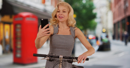 Pretty cyclist in London England checks mobile phone for directions