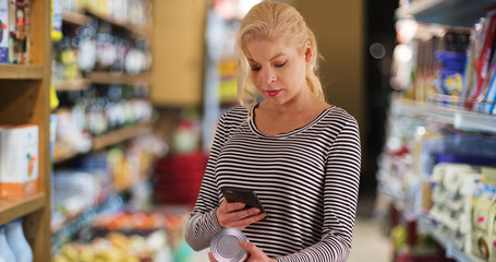 Woman at the grocery store looking up nutrition facts on smartphone