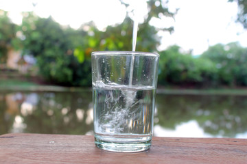 Close up pouring purified fresh drink water from the bottle on wooden table with nature background