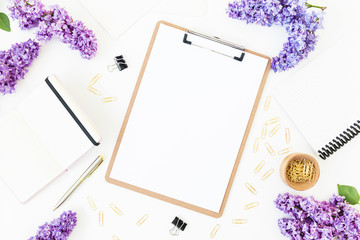 Workplace composition with clipboard, diary,, branches of lilac flowers and accessories on white background. Flat lay, top view.