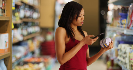 Black woman at supermarket taking picture of nutritional facts label with phone