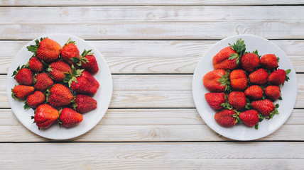 Strawberries on a two white plates top view, red berries on a white wooden background, fresh strawberries on a rustic boards, vegetarian food, copy space.