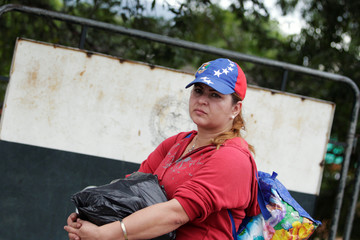 A woman holds her luggage as she tries to cross into Colombia from Venezuela through the Simon Bolivar international bridge in Cucuta