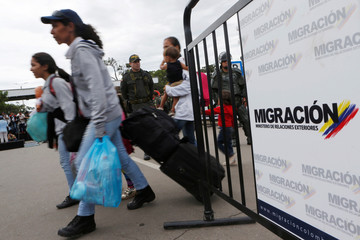 Venezuelan migrants carry their luggage to cross from Venezuela to Colombia via the Simon Bolivar international bridge in Cucuta