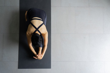 Young woman practicing yoga in  gray background.Young people do yoga indoor.Top view of beautiful young fitness woman working out .