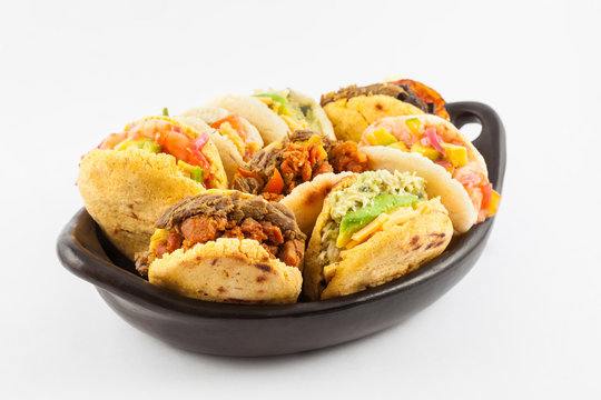 Arepas with assorted fillings served in a black ceramic dish on white background
