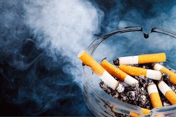 Ashtray and smoked cigarettes on backgrouund