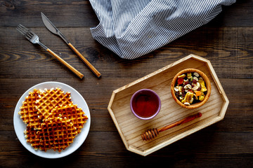 Round belgian waffles for breakfast. Breakfast in bed. Waffles on plate. Honey and dried fruits in tray, knife and fork, tablecloth on dark wooden background top view