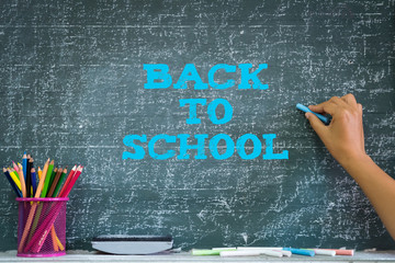 Education or back to school Concept. Woman hand holding chalk with pencils box, chalk, eraser over chalkboard background.