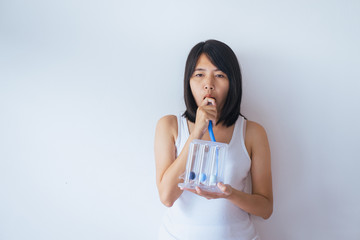 Patient asian woman using incentivespirometer or three balls for stimulate lung