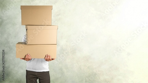 delivery man carrying stacked boxes in front stock photo and