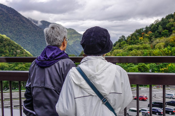 An old couple looking at mountains