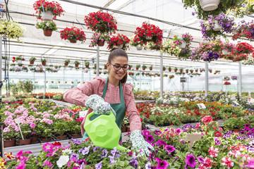 Girl in botanical garden watering from bin colorfull flowers