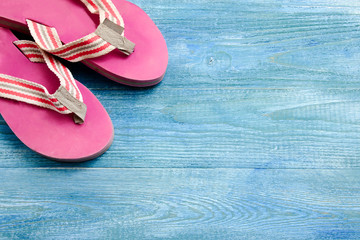 Pink slippers on a blue wooden background, summer background and holiday concept