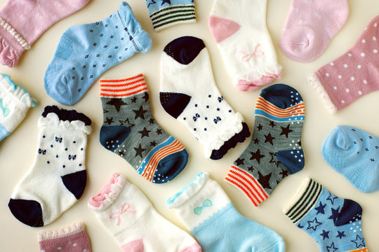 Baby socks on white background. Many socks for baby are scattered on a white background. View from above. Clothes for children from jersey.