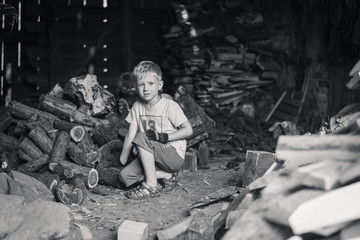 Little boy working in a shed with wood