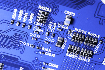 Macro shot of a Circuitboard with resistors microchips and electronic components. Computer hardware technology. Integrated communication processor in blue tones. Semiconductor. PCB. Closeup