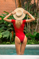 Fashion portrait of a beautiful young woman in sexy red swimsuit standing in pool and correct vintage straw hat. Hot sunny day. Tropic island vacation. Summer travel girl, active hipster lifestyle..