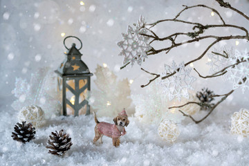 Toy dog Labrador in the frosty winter wonderland with snowfall and magic lights.  New year greetings concept